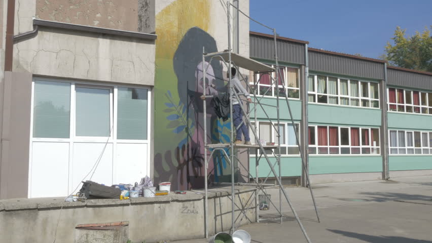 Artist On Scaffold Painting Graffiti Or Mural On The Wall With ...
