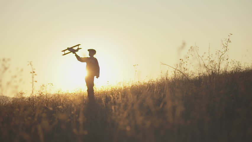 Happy kid playing with toy airplane against orange sun summer sky background. Boy playing airplane on a summer field. Best childhood concept.