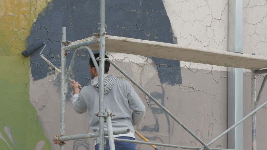 Urban Painter Standing On Scaffold And Painting Mural On Building ...
