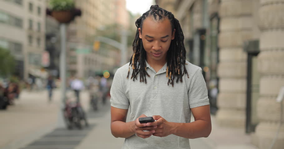 Young man walking New York City street texting cell phone | Shutterstock HD Video #12917282