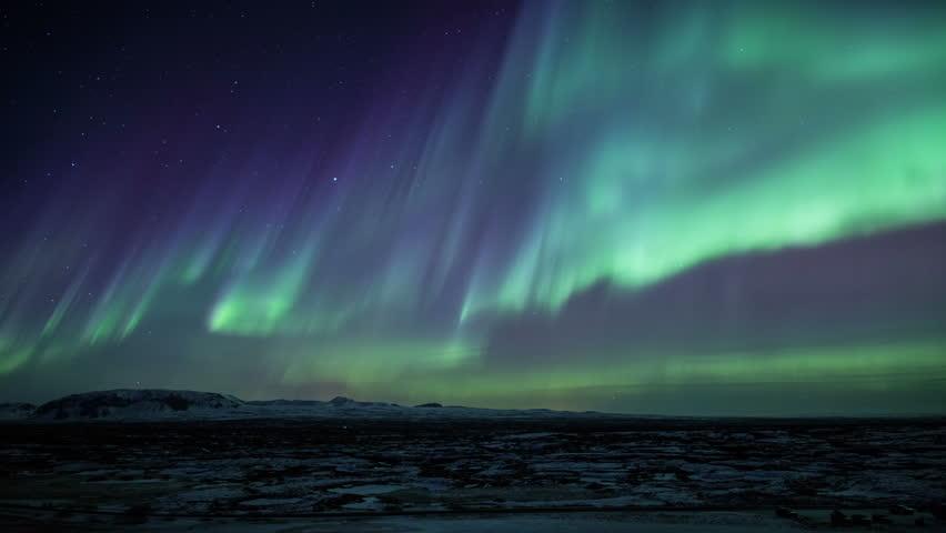 Strong bright Aurora Borealis snow covered lava field mountains Thingvellir Iceland realistic movement 4k