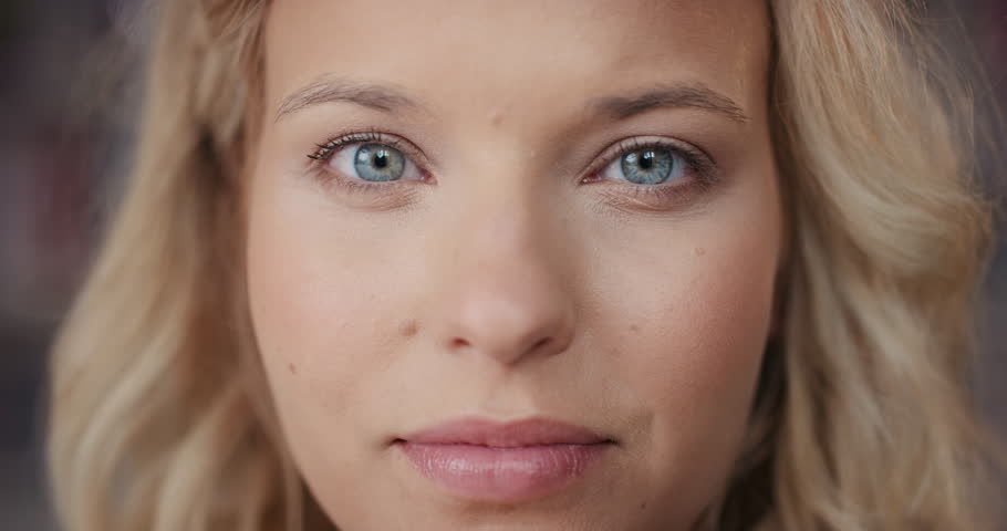 Dramatic Close up of beautiful blonde woman with bright blue eyes portrait happy smiling slow motion soft natural light on face center crop