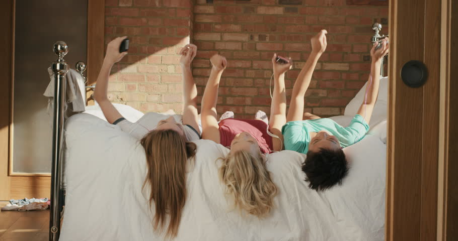 Diverse Girl Friends hanging out at home dancing to music on smartphone in pajamas on bed in teenage bedroom
