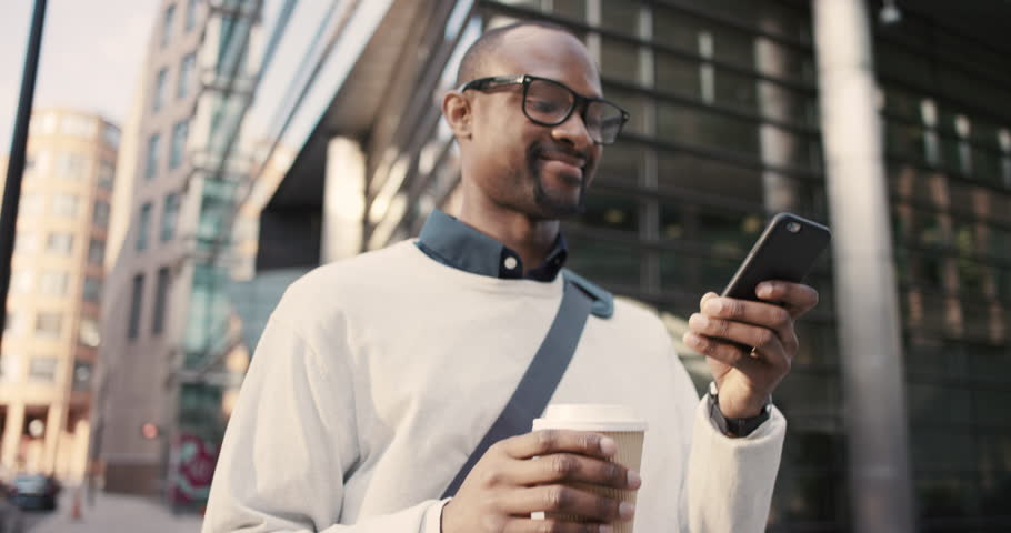African American Man sms texting using app on smart phone in city. Handsome young businessman drinking coffee using smartphone smiling happy. Urban male professional commuting in his 20s
