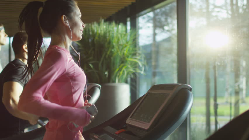 Attractive caucasian girl running on the treadmill in the sport gym with phone and earphones. Shot on RED Cinema Camera in 4K (UHD). | Shutterstock Video #13216154