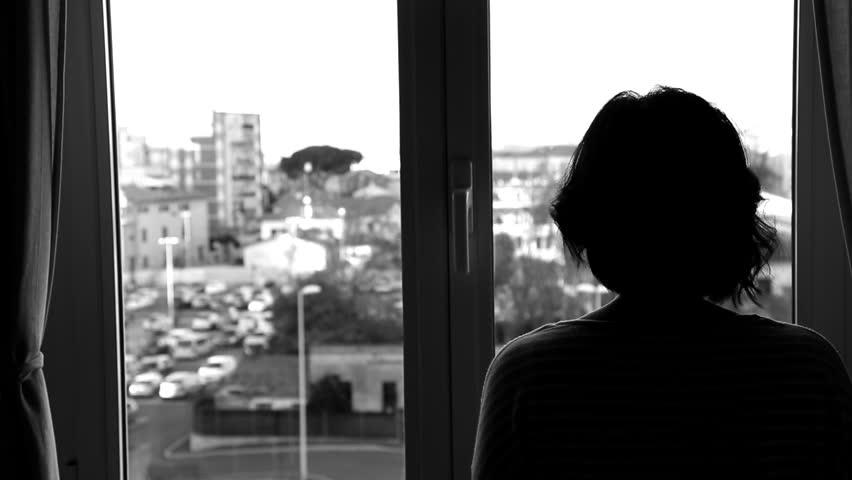 A woman looking out of a window | Shutterstock HD Video #13247207