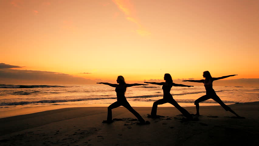Three slim athletic girls in silhouette practicing a healthy lifestyle with yoga on the beach at sunrise