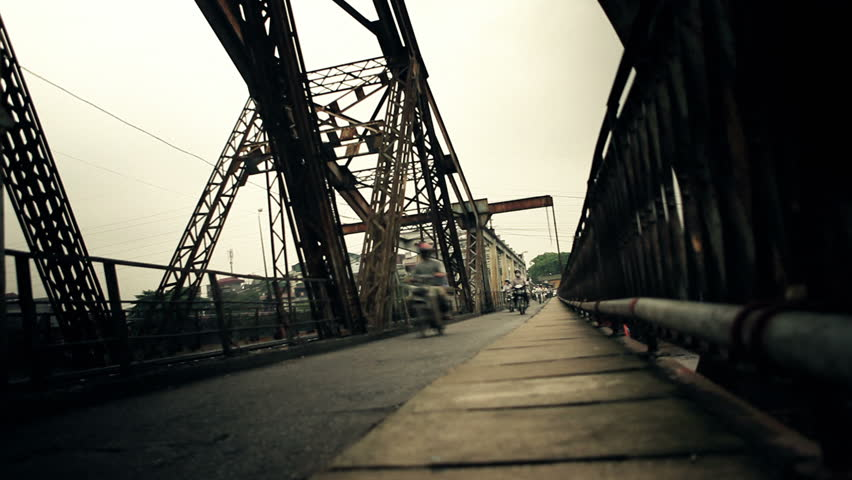 Endless flow of motorbikes shot in time lapse on steel construction bridge