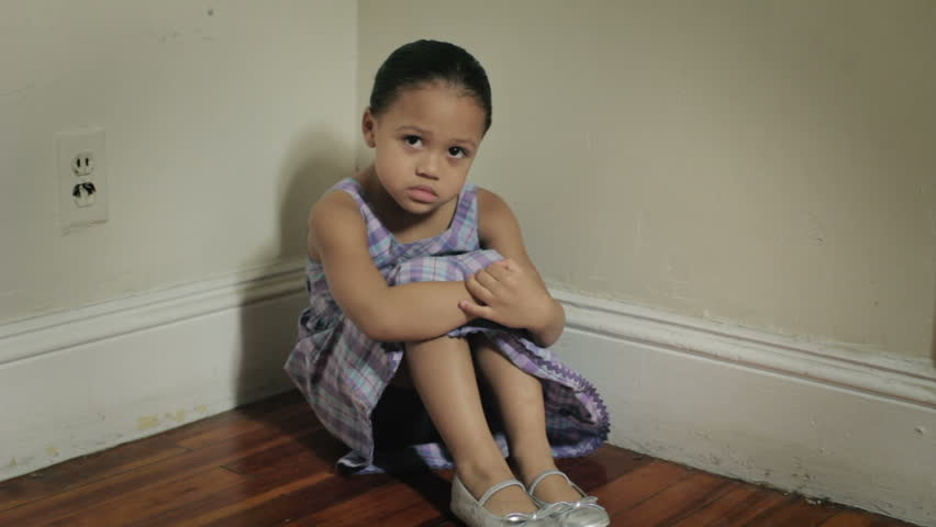 Sad child sitting alone at home, child neglect or abuse concept