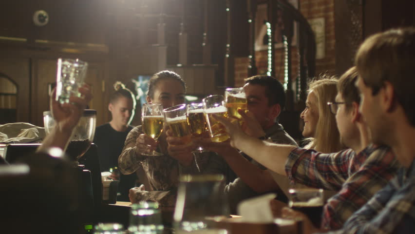 Friends do toasts, drink beer and cocktails while having a good time together at a bar. Shot on RED Cinema Camera in 4K (UHD). | Shutterstock Video #13390304