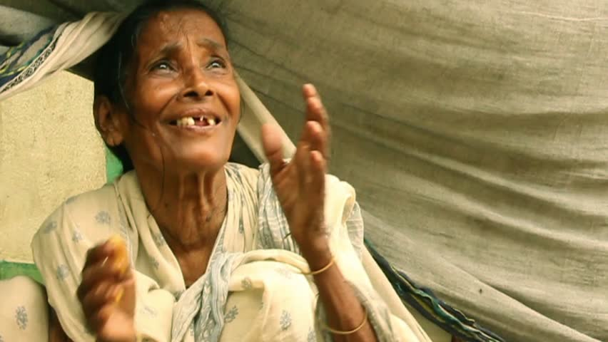 Elderly Indian woman smiles and fold hands in gratitude upon receiving some vegetarian food. She has been put out of home by a big flood #13707548