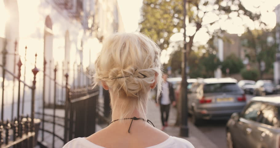 Beautiful blonde walking though city on journey to destination from behind