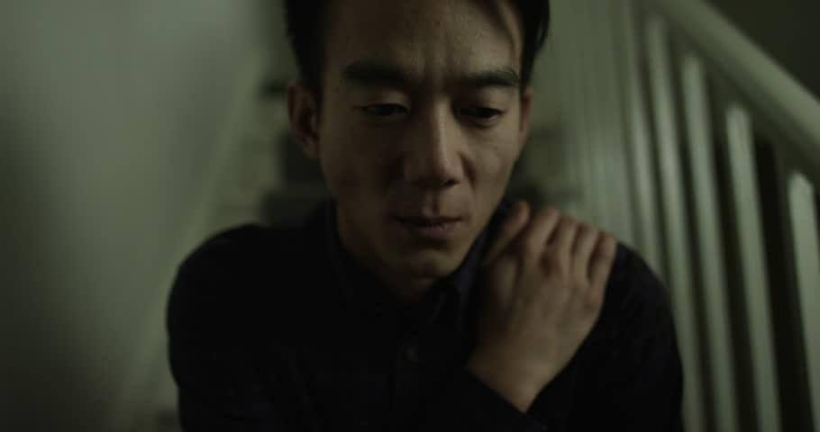 Depressed, sad Asian man looking at camera. Shot on RED Epic.