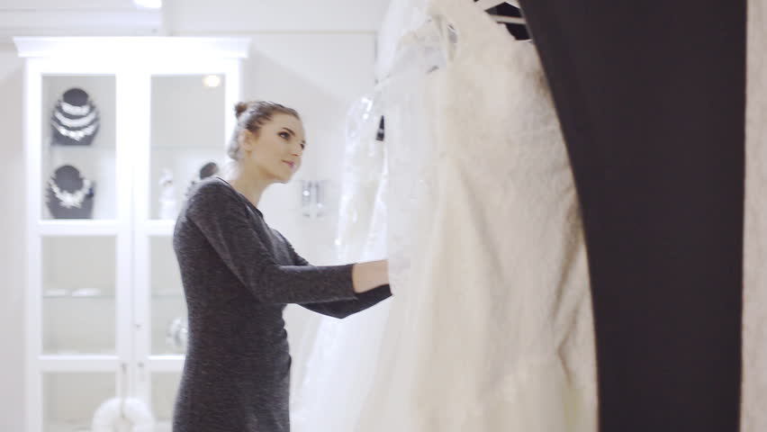 Woman chooses wedding gown at bridal boutique | Shutterstock HD Video #13939010