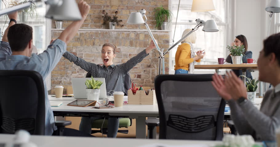 Business woman with arms raised celebrating success watching sport victory on laptop diverse people group clapping expressing excitement in office | Shutterstock Video #13947473