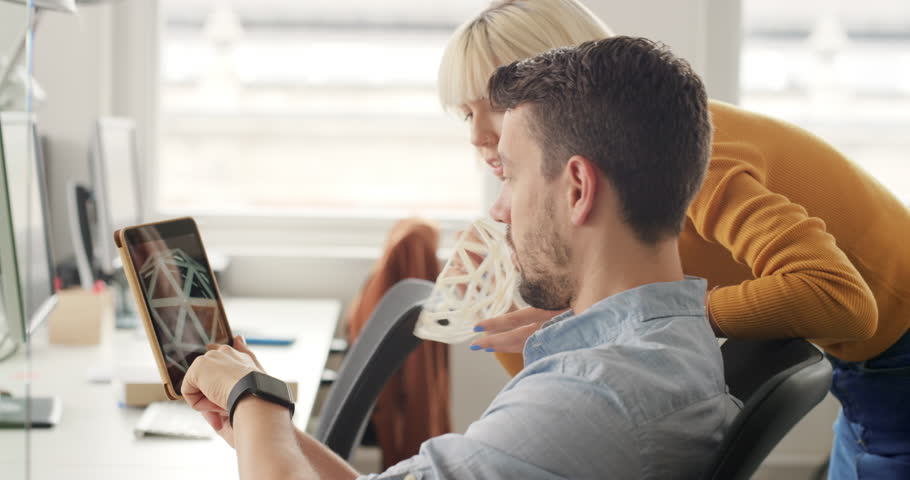 Business woman showing 3d printed object in Creative business team meeting in gender neutral start up office team leader pointing at screen discussing 3d printing technology | Shutterstock Video #13949264