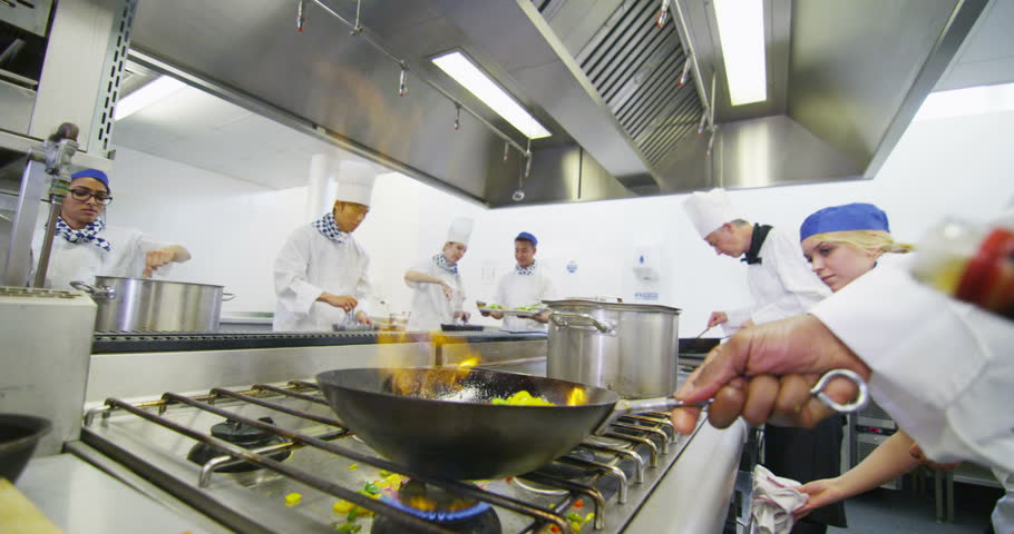 chefs preparing food ready for service in a commercial kitchen shot