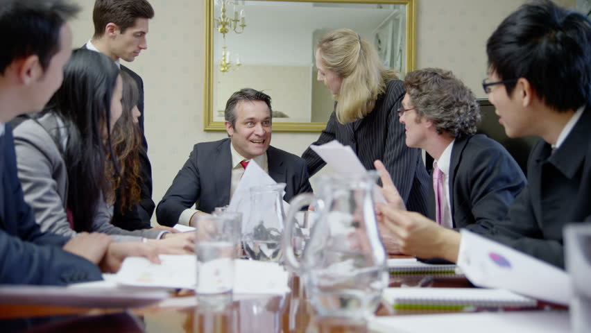 4k / Ultra HD version Diverse team of professionals, sitting around a conference table throw their papers into the air to celebrate some good news. In slow motion. Shot on RED Epic | Shutterstock HD Video #14049341