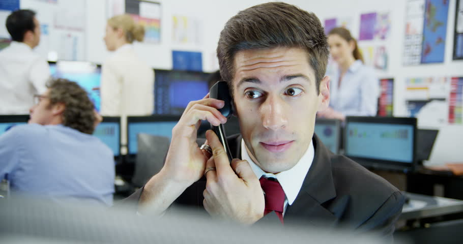 4k / Ultra HD version Young and ambitious stock market trader is doing a deal over the phone in a busy office filled with computers. The rest of his team are hard at work | Shutterstock HD Video #14053655