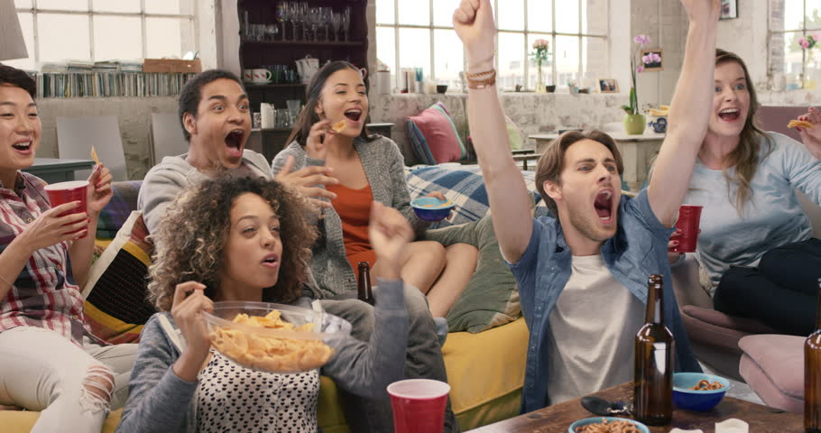 Happy diverse group of student sports fans throwing arms up in excitement celebrating goal watching sports event on TV together bonding as friends eating snacks drinking beer | Shutterstock Video #14075135