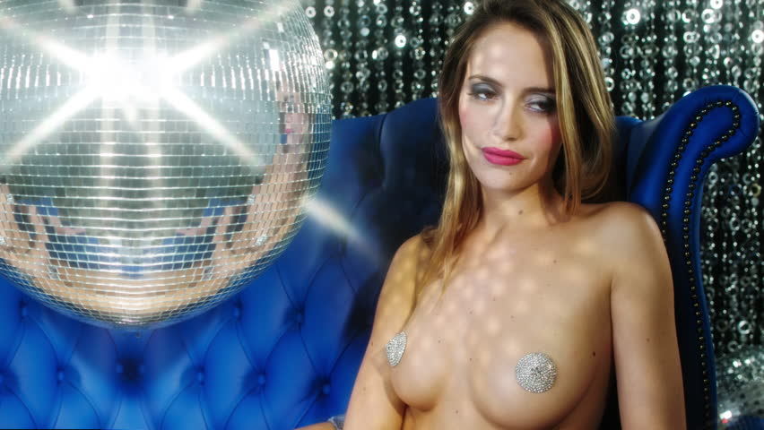 stunning sexy disco woman with silver nipple tassels surrounded by disco balls