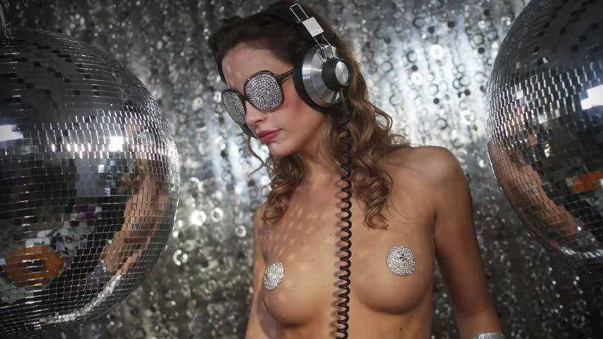 stunning sexy disco dancing woman with silver nipple tassels surrounded by disco balls