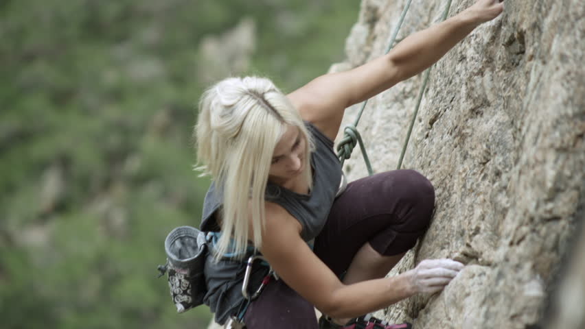 Woman rock climbing and topping out.