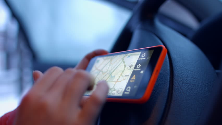 Minsk, Belarus - January 17, 2016: The girl behind the wheel of a car looking map of the city on a mobile phone. 4K 30fps ProRes (HQ) | Shutterstock HD Video #14330509