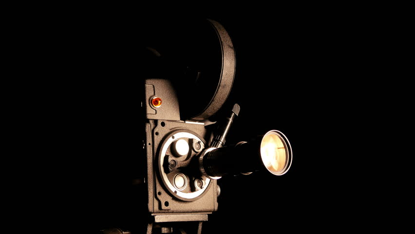 vintage hollywood movie camera in front of black backdrop