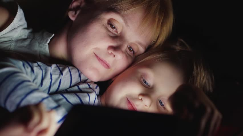 Mum with a blonde girl enjoying tablet. Lying side by side face to face, the light from the tablet screen illuminates their faces | Shutterstock HD Video #14395870