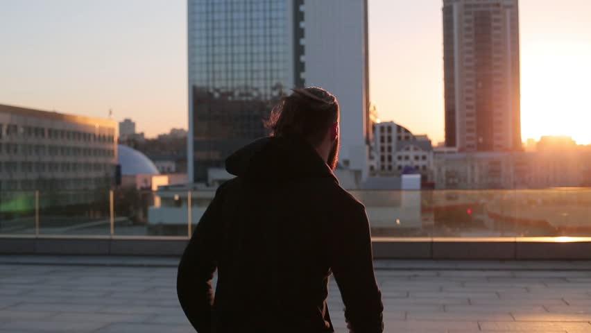 Man running at sunset in city.