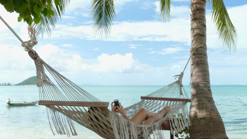 Woman using mobile phone in a hammock on the beach | Shutterstock HD Video #14566666