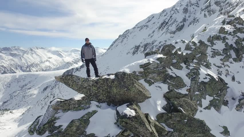 Beautiful Epic Scale Mountain Range Man Standing On Top Of Cliff Edge Snow Winter Landscape Nature Success Accomplishment Opportunity Concept Aerial Flight
