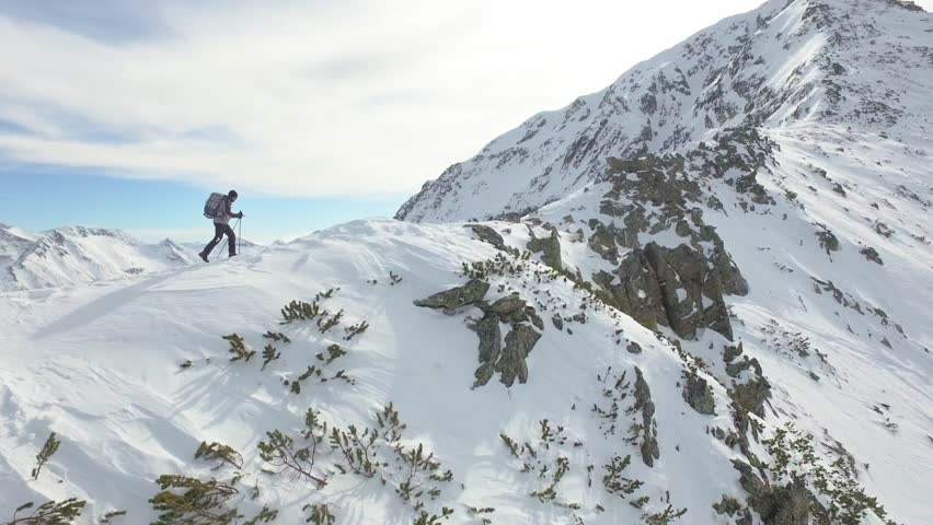 Young Man Walking Up Mountain Slope Backpacking Winter Hike Extreme Conditions Swiss Alps  Aerial Drone Flight Footage