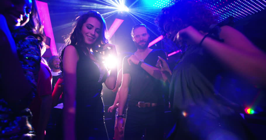 Party flythrough shot of young multi-ethnic group of people and friends dancing to cool music with disco lights in a nightclub for entertainment