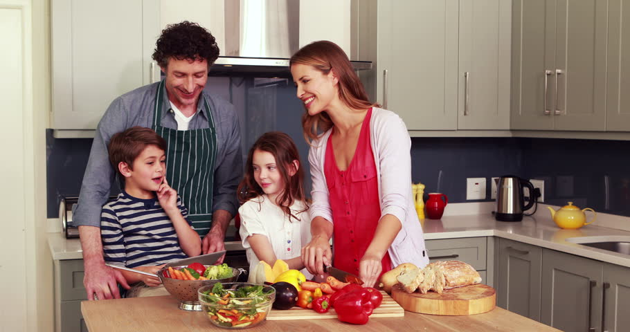 happy family preparing vegetables together in the kitchen stock,