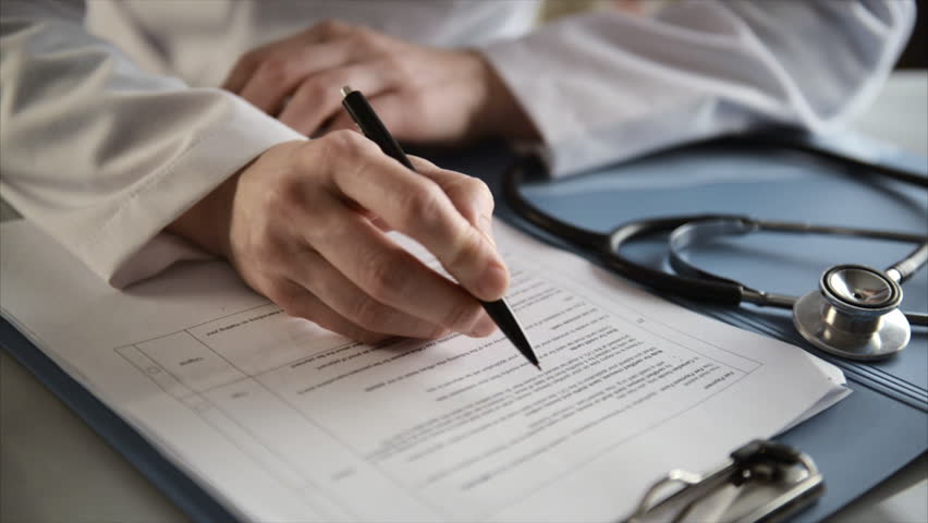 Female doctor doing paperwork in the office. Young therapist filling medical checklist sitting at the desk. Health care and insurance concept. #14792044