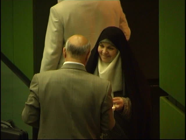 Parliament, Tehran, Iran - 2005 - This clip shows Iranian politician and MP Mrs. Rafat Bayat talking to colleagues while a speech can be heard in Farsi.