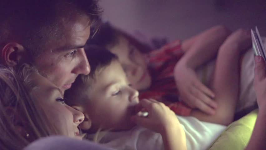 Happy family- Father, mother and Two kids lying down on the sofa and using tablet pc at night. Family watching movie on tablet computer in a dark room. HD 1080p, slow motion 240 fps, high speed camera