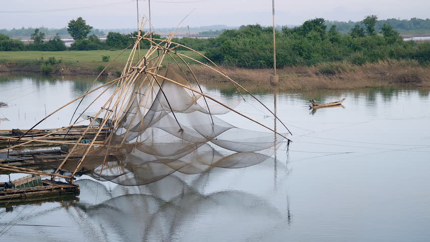 Reflection Of Chinese Fishing Nets In A Lake And Fisherman In A ...