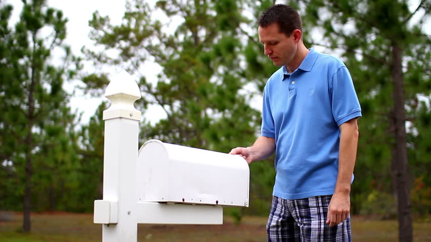 A worried man gets his mail outside of his house.