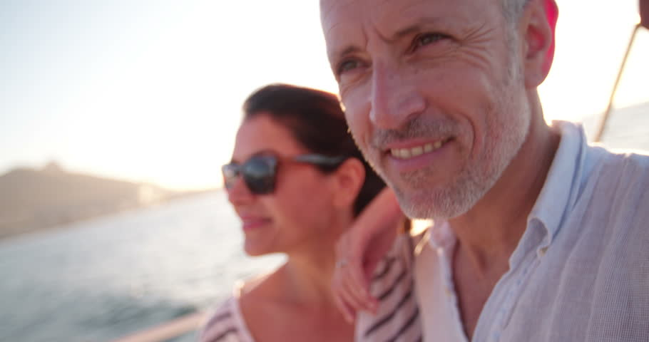 Close up shot of a retired couple looking lovingly at the ocean while enjoying a cruise on a yacht with clear blue sky and bright afternoon sunflare
