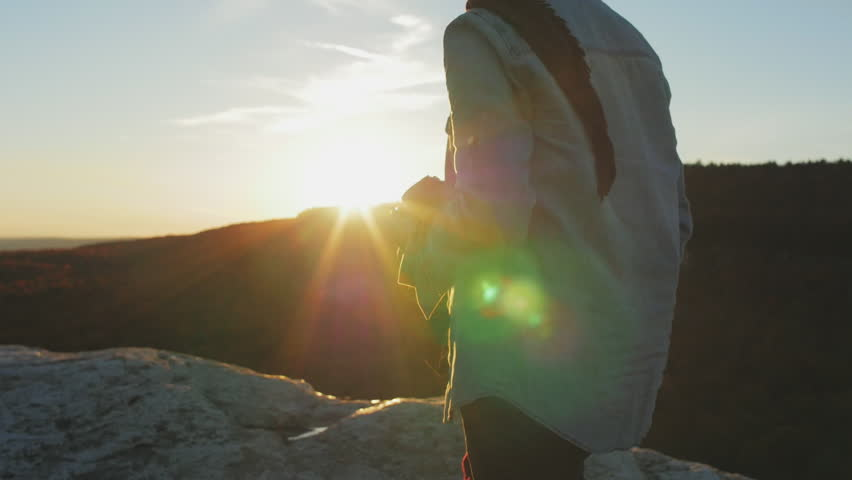 Slow motion of girl standing on mountain top taking photo at sunset | Shutterstock HD Video #14992750