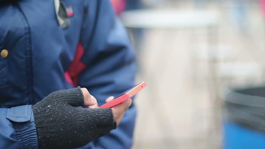 Male hand in old fingerless gloves using touch phone, poor man texting message | Shutterstock HD Video #15098149