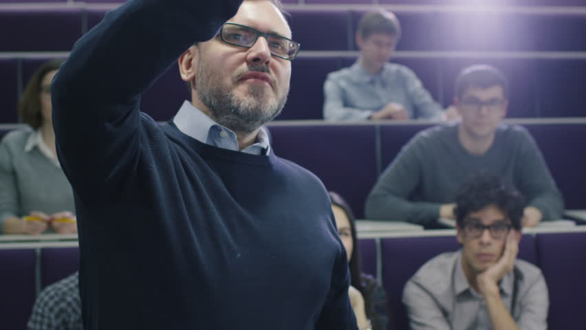 College professor is teaching a class of multi-ethnic students while pointing the desk with a marker. Shot on RED Cinema Camera in 4K (UHD).