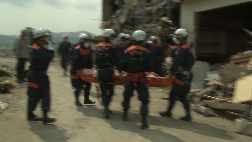 RIKUZENTAKATA, JAPAN - MARCH 2011: Japan Tsunami Aftermath - Rescue Team Attend To Dead Body In Rikuzentakata City - Full HD 1920x1080 30p. #15202819
