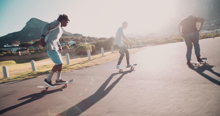 Multi-Ethnic group of skater friends skateboarding down road at seaside together during sunset | Shutterstock Video #15362896