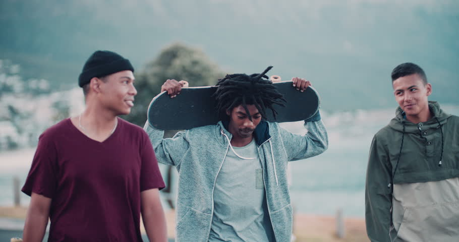 Multi-Ethnic group of skater friends hanging out, holding skateboards and smiling with one holding skateboard behind head with both hands at seaside | Shutterstock Video #15362983