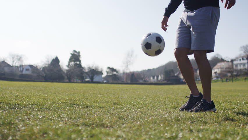 Baby With Father Playing With Soccer Ball On The Grass
