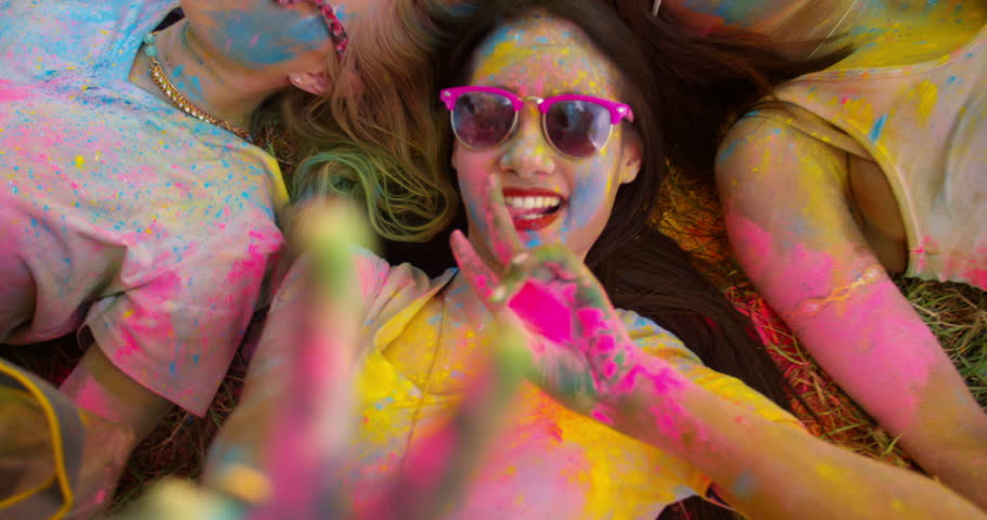 Multi-Ethnic group covered in Holi powder lay in grass laughing and looking up and gesturing peace sign to the camera in a park at a Holi festival in the summer   Shutterstock Video #15427240